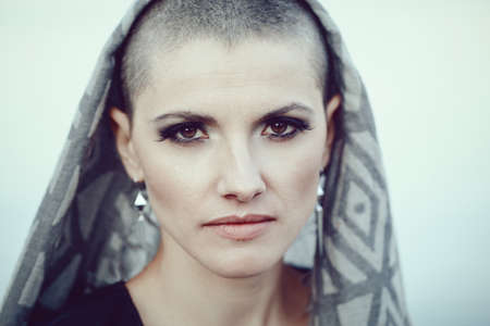Portrait of sad beautiful Caucasian white young bald girl woman with shaved hair head, scarf cover, looking in camera, toned with filters in blue green color