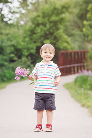 toddler walking: Portrait of a cute adorable funny little smiling boy toddler walking in park with lilac purple pink flowers in hands on bright summer day, mothers day holiday concept Stock Photo
