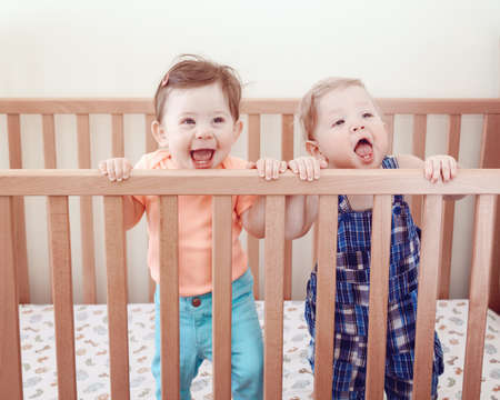 nine  months: Portrait of two cute adorable funny babies siblings friends of nine months standing in bed crib smiling laughing, looking in camera away, lifestyle everyday sweet candid moment