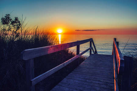 pinery: Beautiful evening sunset landscape at Canadian Ontario lake Huron in Pinery Park, orange blue red sky sun. Amazing summer sunset view on the beach. Dunes, grass, wooden stair leading to water