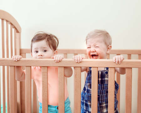 nine  months: Portrait of two cute adorable funny babies siblings friends of nine months standing in bed crib chewing eating sucking wooden sides creying, looking in camera away, lifestyle everyday sweet candid moment