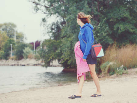 portrait of woman girl walking on beach with lunchbox and blanket on cold windy summer autumn day with her face away from camera, retro vintage old film effect, hipster style, copyspace place for text