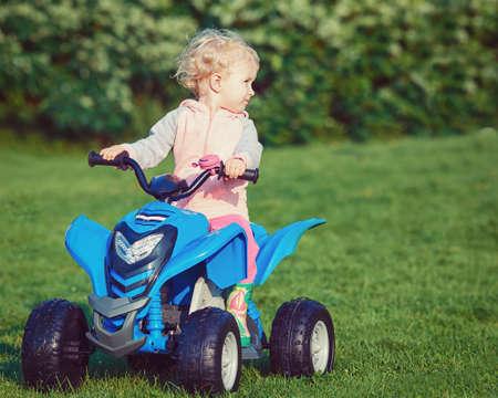 Portret van leuk aanbiddelijk gelukkig klein blond Kaukasisch jongensmeisjeskind die blauwe elektrische auto in park buiten op zonnige winderige de zomerdag drijven Stockfoto