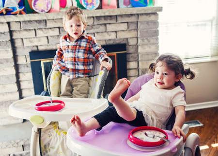 comiendo cereal: Retrato de los niños caucásicos adorables lindos gemelos hermanos que se sienta en la silla alta de comer cereales temprano por la mañana, el estilo de vida cotidiana momentos espontáneos
