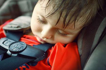かわいいかわいい男の子幼児のポートレート、クローズ アップが疲れているし、眠っている彼の旅行、安全保護コンセプト carseat にベルト付き