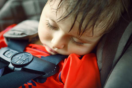 Closeup portrait of a cute adorable little boy toddler tired and sleeping belted in carseat on his trip, safety protection concept
