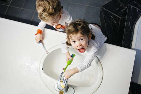Nahaufnahmeportrait der Zwillinge Kinder Kind Junge Mädchen im Badezimmer Toilette waschen Gesicht Hände Zähne mit toothbrash mit Wasser, Lifestyle nach Hause Stil, alltägliche Momente, Ansicht von oben spielen Bürsten Standard-Bild