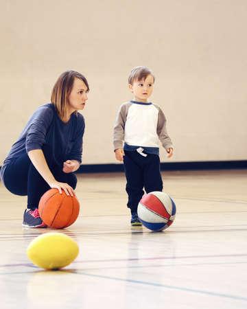 Moeder en zoon spelen met bal in de sportschool, vroege kind gezonde ontwikkeling, familie plezier, coaching en training concept, Stockfoto