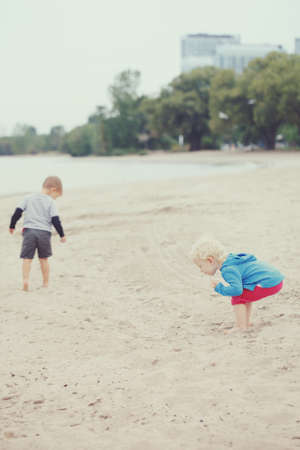 Two children kids toddlers boy girl walking on sand sea lake ocean beach looking for something interesting,  picking seashells, talking and playing together, best friends forever, toned with instagram filters, retro old vintage effect, hipster style, ever Stok Fotoğraf