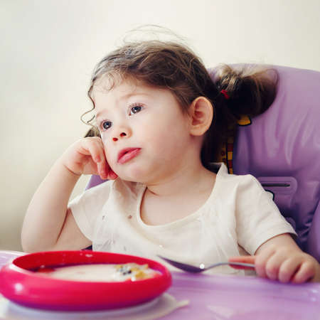 high chair: Portrait of cute bored Caucasian child kid girl sitting in high chair eating cereal with spoon early morning, everyday lifestyle candid moments