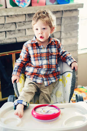 Portrait of cute adorable Caucasian child kid boy standing in high chair with leg on table early morning, everyday lifestyle candid funny moment