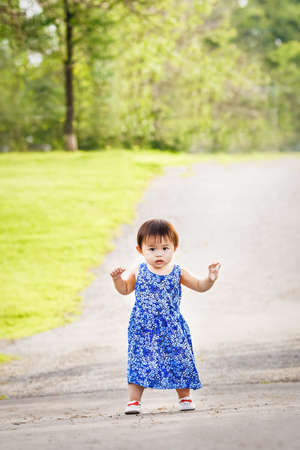 Portrait of a cute adorable little Asian girl child, one two years old, in blue dress and white shoes walking running in park outside on summer day, concept of first baby steps