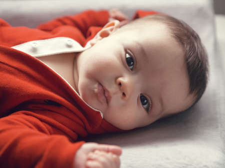 looking directly at camera: Closeup portrait of cute adorable Caucasian baby boy girl with black brown eyes in red hoodie shirt on changing table looking directly in camera, natural light indoors