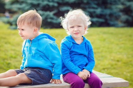 Portraits of Caucasian cute boy and girl friends sitting together in park outside on summer day, backlit with sun from behind Stock Photo