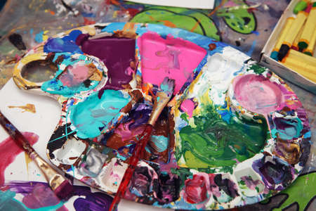 Beautiful colorful textured background, paint strokes on paper and left overs residues of paints in palette colour array on table, spots and blotches stains
