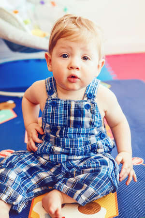 romper: Portrait of cute adorable blonde Caucasian smiling baby boy with brown eyes in blue romper sitting on floor in kids room looking in camera, natural window light, lifestyle