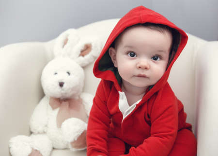 Closeup portrait of cute adorable Caucasian baby boy girl with black brown eyes in red hoodie shirt sitting in chair with toy looking directly in camera Stock Photo