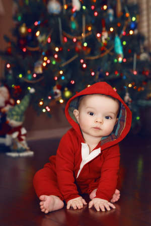 Cute adorable Caucasian baby infant with dark black eyes in red costume hoodie sitting by New Year Tree looking directly in camera. Happy holidays. Winter holidays. Baby first Christmas. Stock Photo