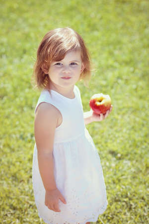 difficult lives: Closeup portrait of a adorable funny toddler child girl holding eating apple in park outside on summer day Stock Photo