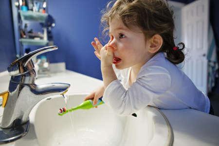 Close-up portret van kind peutermeisje in badkamer toilet wassen gezicht handen borstelen tanden met toothbrash spelen met water, lifestyle huis stijl, alledaagse moment ochtendroutine Stockfoto
