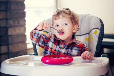 Portrait of cute adorable Caucasian child kid boy sitting in high chair eating cereal with spoon early morning, everyday lifestyle candid moments