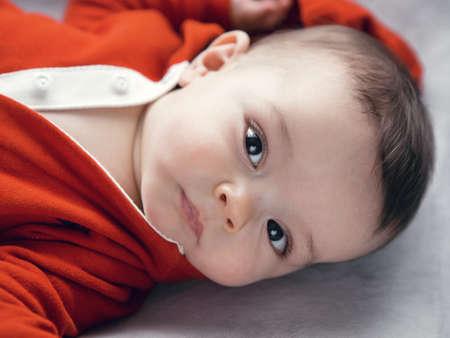 Close-up portret van schattige schattige Kaukasische baby jongen meisje met zwarte bruine ogen in rode hoodie overhemd op het veranderen van tafel te kijken direct in de camera, natuurlijk licht binnen