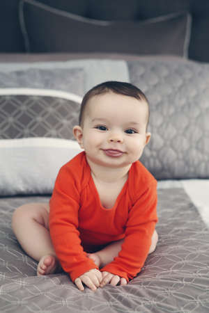 Portrait of cute adorable Caucasian smiling baby boy girl with black eyes in orange  sitting on bed looking directly in camera shwoing tongue, natural window light, lifestyle