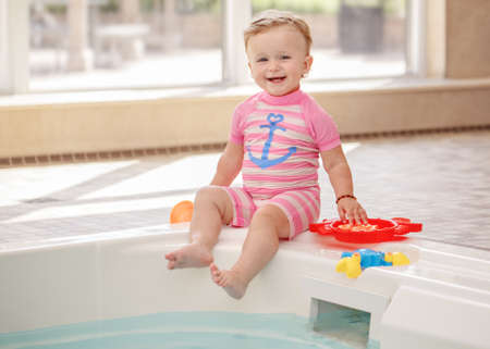 Portrait of white Caucasian baby girl laughing sitting on swimming-pool nosing looking in camera, training to swim, healthy active lifestyle