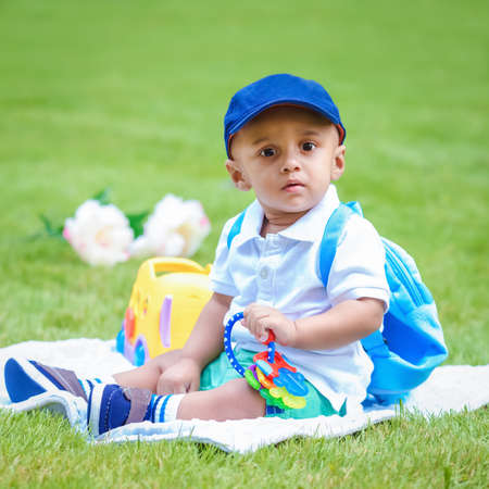 Portrait of cute adorable little indian mixed race infant boy in white shirt sitting on ground with blue backpack schoolbag and toys in park outside looking in camera, back to school concept