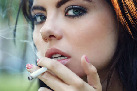 Closeup portrait of white Caucasian beautiful young brunette woman with light blue green eyes smoking cigarette looking in camera, toned with filters