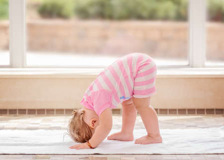 Portrait of cute adorable white Caucasian baby girl doing physical fitness exercises yoga alone standing on floor in swimming pool Archivio Fotografico