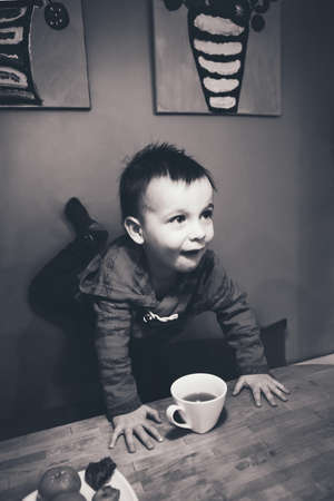 Close-up black and white candid natural portrait of cute adorable little boy toddler in kitchen indoors making funny face, lifestyle documentary style, grainy film effect