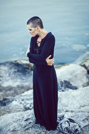 Portrait of sad beautiful Caucasian white young bald girl woman with shaved hair head standing by water lake looking away 写真素材