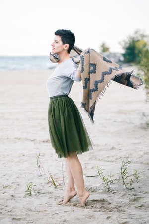 회색 셔츠, 녹색 올리브 투투 얇은 명주 그물, 짧은 목발에 큰 목도리 스카프와 함께 아름 다운 백인 백색 갈색 머리 여자의 초상화 맨발로 맨발로 멀리 찾고, 자유의 정신에 해변에 서있는