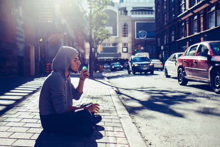 Conceptual art portrait of beautiful young middle east brunette man with beard, wearing grey hoodie, sitting on ground in street outside in city blowing soap bubbles