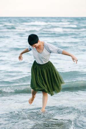 회색 셔츠, 녹색 올리브 투투 얇은 명주 그물 치마에 짧은 머리를 가진 아름 다운 미소 백인 백색 갈색 머리 여자의 초상화 맨발로 바닷물 해변에 서있는의 초상화