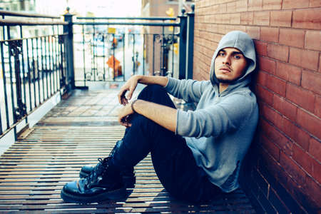 infernal: Conceptual art portrait of beautiful handsome young middle east brunette man with beard, wearing grey hoodie, sitting on staircase outside in city looking away
