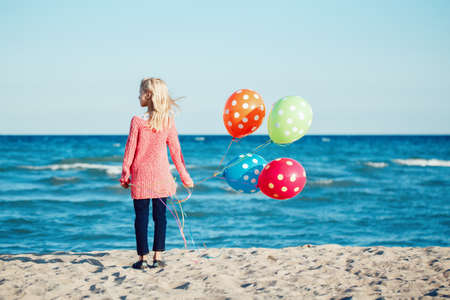 adulthood: Portrait of pensive teenager white Caucasian child kid with colorful bunch of  balloons, standing on beach on sunset looking away, autumn fall season, happy lifestyle childhood concept Stock Photo
