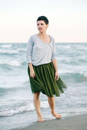 회색 셔츠, 녹색 올리브 투투 얇은 명주 그물 치마에 짧은 머리를 가진 아름 다운 하얀 백인 갈색 머리 여자의 초상화 맨발로 멀리 찾고 바다 물에 해변에 서있는