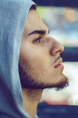 Closeup conceptual art portrait of beautiful handsome young middle east brunette man with blue eyes, beard, wearing blue hoodie, outside in street looking away up