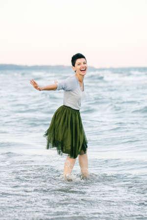 회색 셔츠, 녹색 올리브 투투 얇은 명주 그물 치마에 짧은 머리를 가진 아름 다운 미소 laughing 백인 갈색 머리 여자의 초상화 카메라에서 찾고 바닷물 해변에서 맨발로