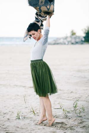 회색 셔츠, 녹색 올리브 투투 얇은 명주 그물, 짧은 목에 큰 목도리 스카프, 닫힌 된 눈을 가진 해변에 맨발로 서와 아름 다운 백인 백색 갈색 머리 여자의 초상화