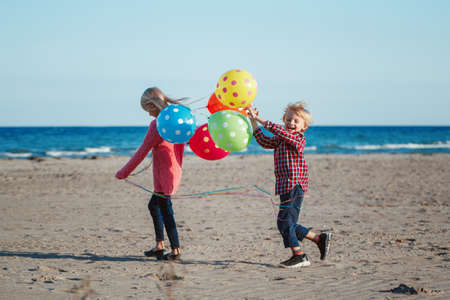 Group portrait of two funny white Caucasian children kids with colorful bunch of  balloons, playing running on beach on sunset, autumn fall season