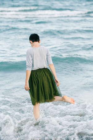 회색 셔츠, 녹색 올리브 투투 얇은 명주 그물 치마에 짧은 머리를 가진 아름 다운 백인 백색 갈색 머리 여자의 초상화 맨발로 바닷물 해변에서 그녀의 다시 카메라에 서있는의 초상화