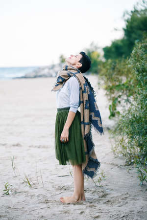 회색 셔츠, 녹색 올리브 투투 얇은 명주 그물, 짧은 목에 큰 목도리 스카프, 하늘에서 찾고 해변에서 맨발로 서와 함께 아름 다운 백인 백색 갈색 머리 여자의 초상화