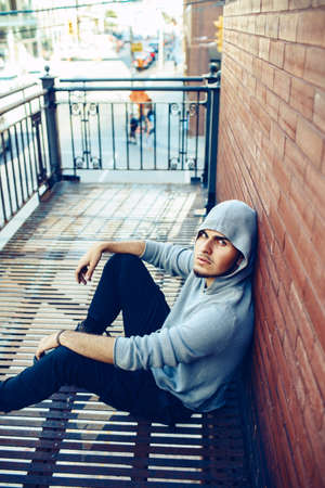 infernal: Conceptual art portrait of beautiful handsome young middle east brunette man with beard, wearing grey hoodie, sitting on staircase outside in city looking up in camera Stock Photo
