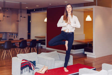 Portrait of slim fit sporty young white Caucasian business woman with long blond hair in white shirt meditating doing yoga exercises on office table at work