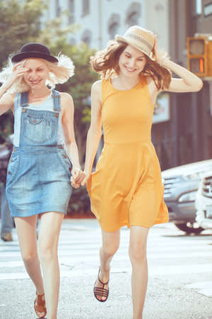 cross street with care: Portrait of two white Caucasian unformal young girls hipster students teenagers friends in dresses, hats, outside running crossing urban city street crowded with cars Stock Photo
