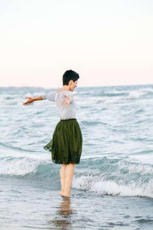 짧은 회색 셔츠에 머리, 녹색 올리브 투투의 얇은 명주 그물 치마, 바다 물에 해변에서 맨발로 서 카메라에 그녀를 다시, 무료 행복한 라이프 스타일을 가진 아름 다운 백인 흰색 갈색 머리 여자의 초상화