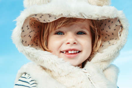 Closeup portrait of cute adorable beautiful funny smiling laughing white blonde Caucasian child kid baby girl with blue eyes in fur coat, looking in camera outside